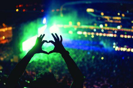 בחורה עושה צורה של לב עם הידיים בהופעה