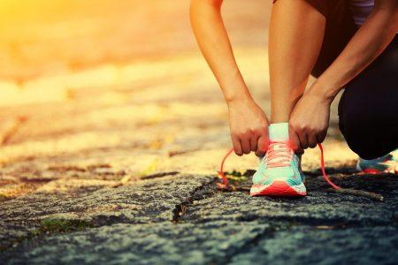 בחורה קושרת שרוכים במהלך ריצה