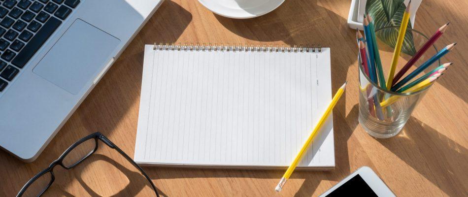 מחברת עפרון ולפטופ על שולחן מעץ